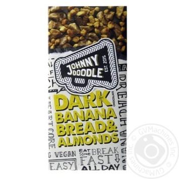 Шоколад чорний посипаний шматочками сушеного Банану та карамелізованих ядер горіха мигдалю Johnny Doodle 150гр